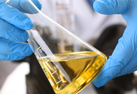 Hands in blue gloves holding a tilted Erlenmeyer flask with gold liquid